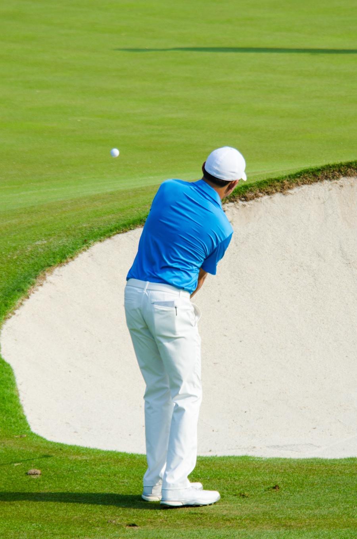 Golfer hitting golf shot.