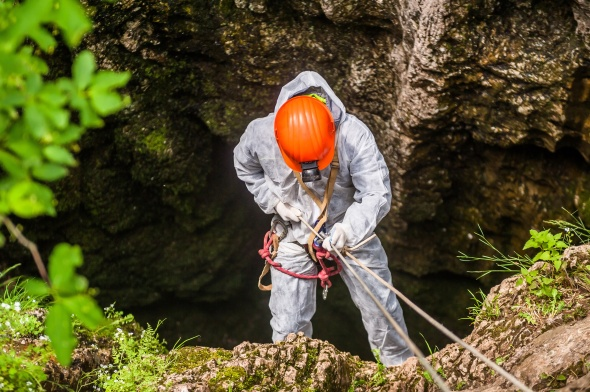 Caver descends into the cave